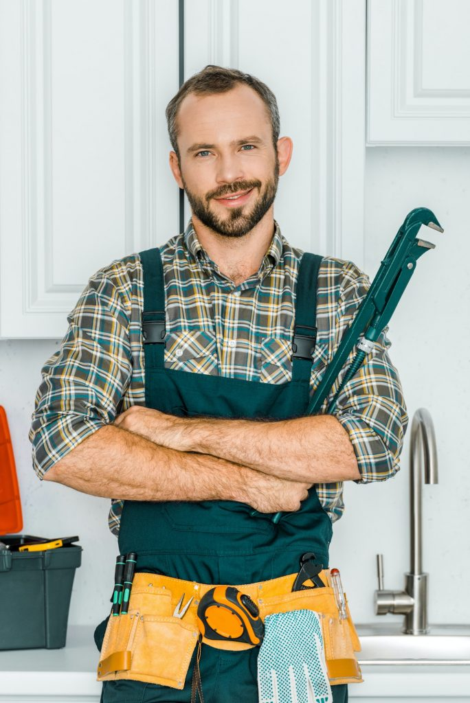handsome plumber holding monkey wrench and looking at camera in kitchen